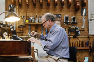 The violin maker is surrounded by change, but making music and instruments is a constant